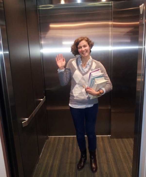 Librarian holding a stack of books smiles and waves from inside the new elevator