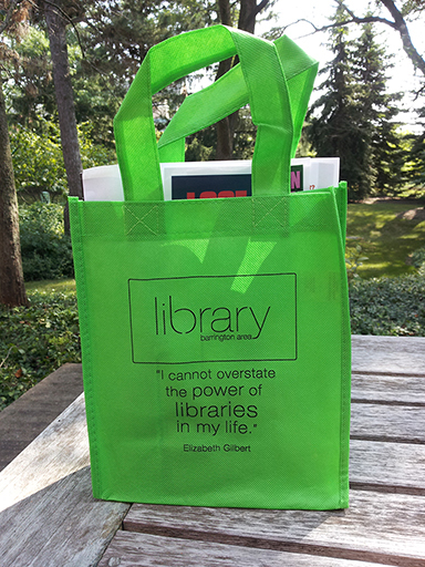 "Lime green small tote bag with wording ""library barrington area I cannot overstate the power of libraries in my life, quote from Elizabeth Gilbert"" Bag is sitting on a wooden table, trees in the backgrouind"
