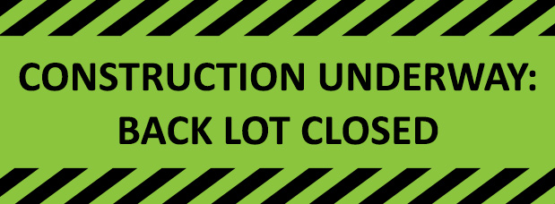 Construction underway, back parking lot closed, green and black striped construction sign